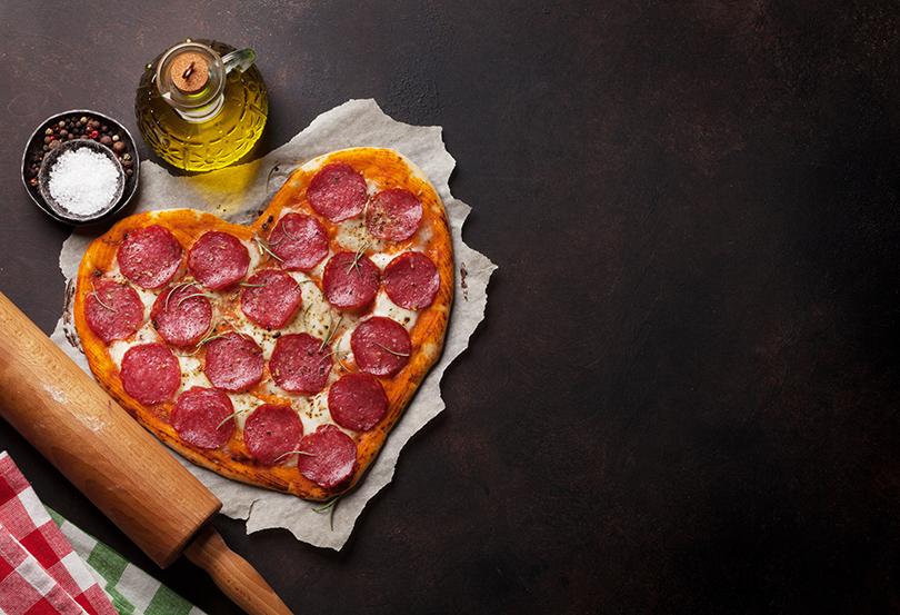 Pizza de calabresa em formato de coração, em uma bancada escura com elementos de culinária incorporando a imagem.