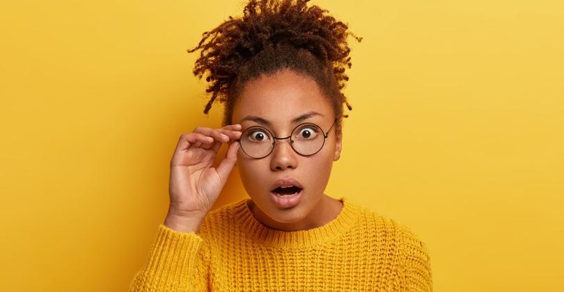 Mulher negra de óculos, com expressão se surpresa, vestindo camiseta amarela sob um fundo amarelo.