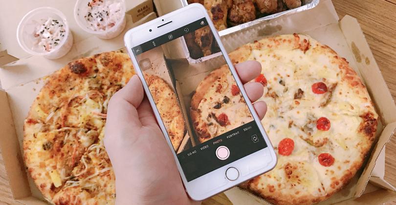 Mão de uma pessoa segurando um celular com a câmera ligada, apontando para as duas pizzas que ele pediu no delivery.