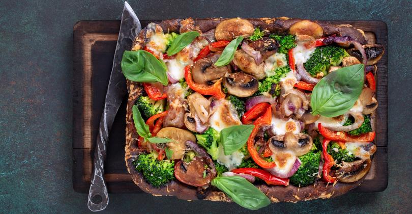 Pizza retangular com recheio de legumes coloridos, sobre uma tábua de madeira escura e uma faca de inox.