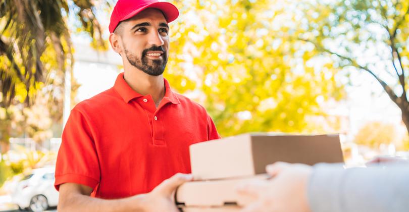 Homem realizando uma entrega de pedido feito via delivery, vestindo camiseta e boné vermelhos, sorrindo.