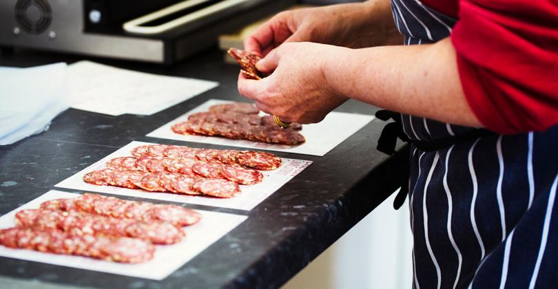 Mãos de um cozinheiro separando salames em sua bancada para iniciar o processo de porcionamento dos ingredientes para pizza.