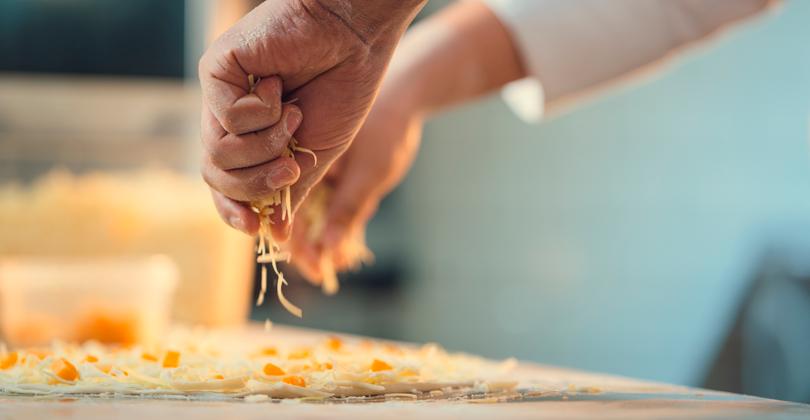 Mãos de um pizzaiolo colocando queijo sobre uma pizza de milho.