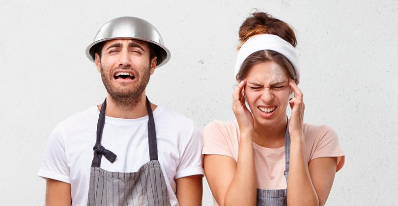 Pizzaiolos preocupados com a dificuldade de porcionar os insumos. Homem com a bacia na cabeça e mulher com as mãos indicando dor de cabeça. Ambos com a expressão de estresse.