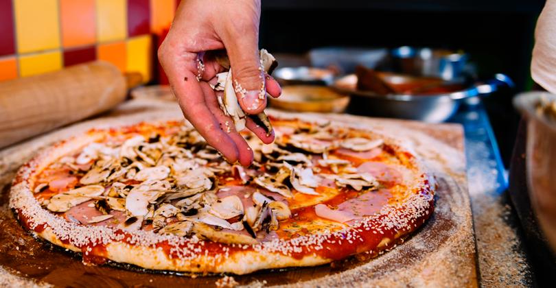 Mãos de um pizzaiolo distribuindo cogumelos sobre uma pizza com borda de gergelim