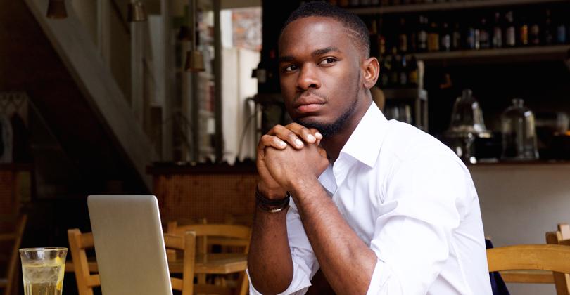 Jovem empreendedor negro, em seu restaurante delivery, pensando sobre o Pixel do Facebook rastreando seus clientes
