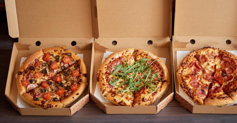 3 caixas com pizza dentro, quentinhas, prontas para serem entregues via delivery.