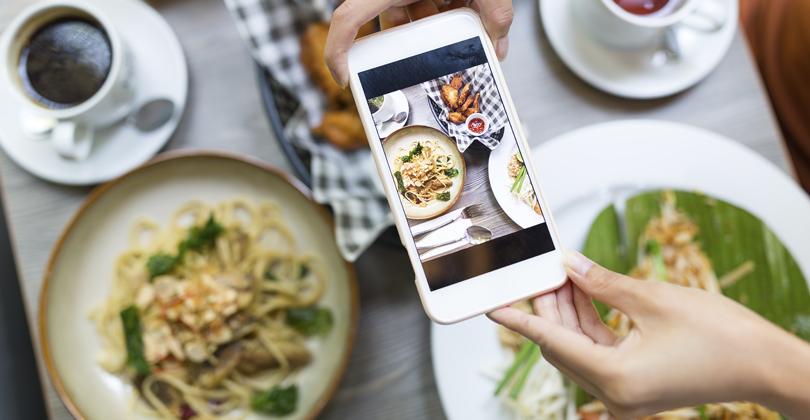Mãos de uma mulher com um telefone fotografando as comidas para seu cardápio que vende